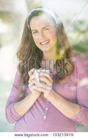 Portrait of happy pregnant woman with coffee by window at home