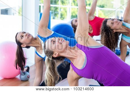 Cropped image of women doing side stretch in fitness studio