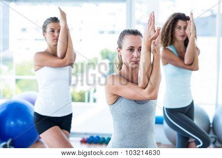 Women doing eagle pose in fitness studio