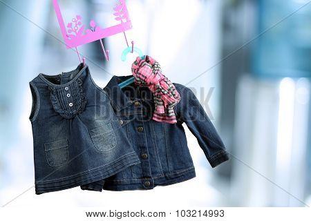 Fashion Baby Dresses Hanging On A Hanger On A Blue  Background