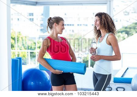 Fit women looking at each other while holding exercise mat and water bottle in fitness studio
