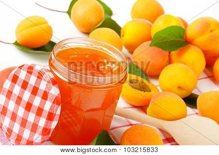 opened jar with apricot jam accompanied by fresh apricots
