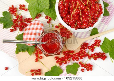overhead view of glass jar with red currant jam standing on the wooden cutting board with spoon and freshly picked red currant