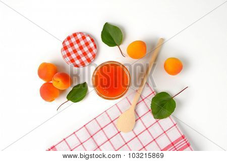 overhead view of glass jar with apricot jam, accompanied by a fresh apricots, napkin and wooden spoon