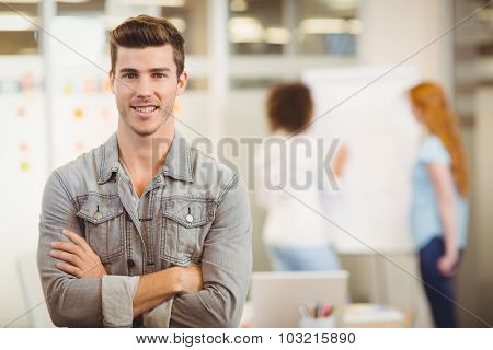 Portrait of smiling businessman with arms crossed standing against female colleagues working office