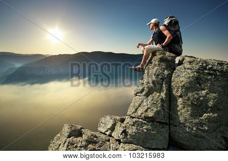 Man tourist on peak of mountain. Travel mountain scene.
