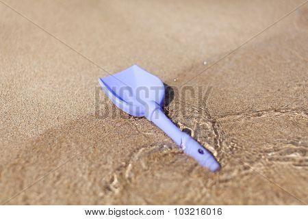 Blue toy beach shovel on sea beach