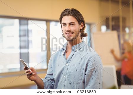 Portrait of confident businessman texting on phone with female colleagues looking at whiteboard in creative office