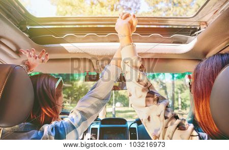Happy women holding hands and raising arms inside of car