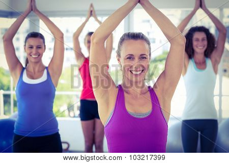 Cheerful women in fitness studio with hands joined overhead while standing