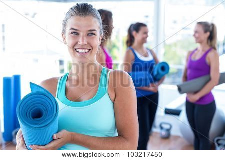 Portrait of cheerful woman holding exercise mat with friends at fitness studio