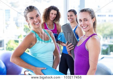 Portrait of attractive women holding exercise mat in fitness studio