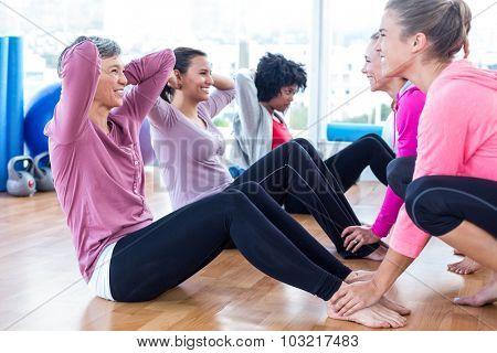 Women helping friends to do sit ups in fitness studio