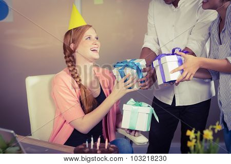 Happy businesswoman receiving birthday gifts from colleagues in office