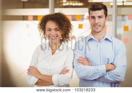 Portrait of confident business people standing with arms crossed in office