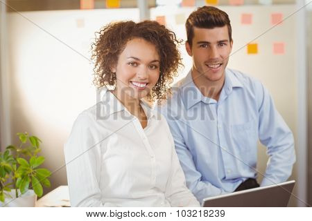 Portait of smiling businesswoman with male colleague in office