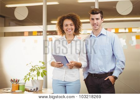Portrait business woman using digital tablet while male colleague looking in office