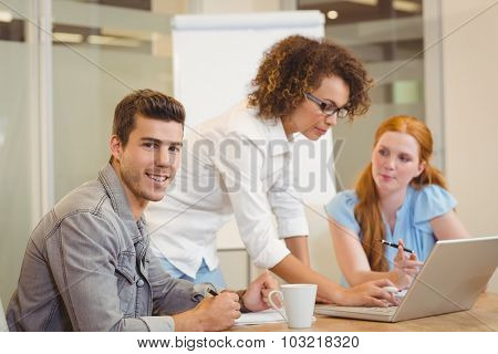 Portrait of handsome businessman with female colleagues in office during meeting