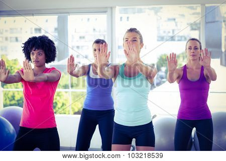 Focused women with arms stretched forward in fitness studio