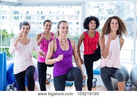 Portrait of smiling women exercising with clasped hands in fitness studio