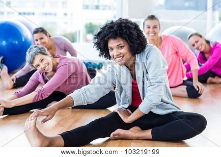Portrait of cheerful fit women touching toes in fitness studio