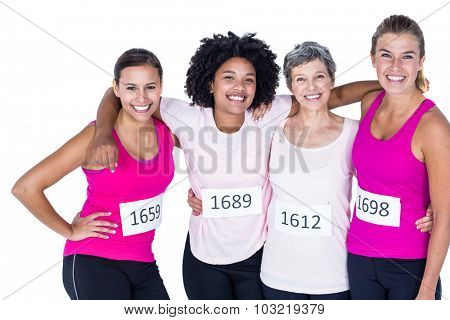 Portrait of happy female athletes with arms around while standing against white background