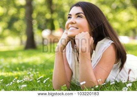 Portrait of thoughtful pretty cheerful woman lying on grassland in park