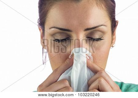 Close-up of woman suffering from blowing nose with tissue on mouth against white background