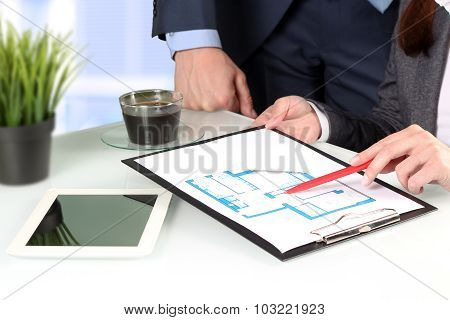 Real-estate Agent Showing House Plans To A Businesssman. Focus on a pen and hand