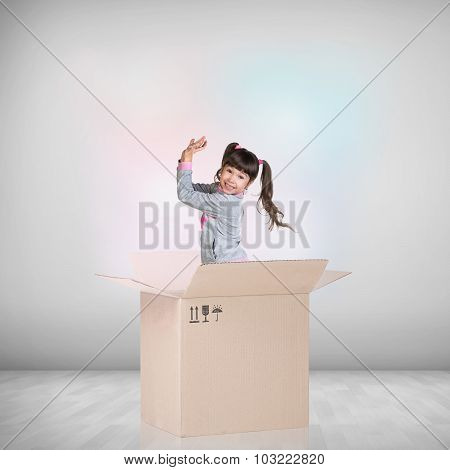 Beautiful little girl inside a cardboard box