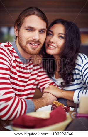 Affectionate dates looking at camera while sitting in cafe