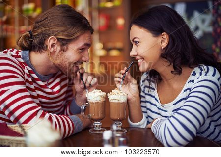 Happy young dates having latte during rest in cafe