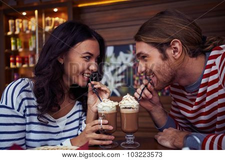 Flirty young couple drinking latte in cafe