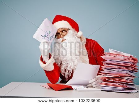Pensive Santa Claus with Christmas letter sitting by table
