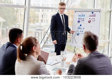 Happy young businessman pointing at chart on board while presenting review of marketing analysis