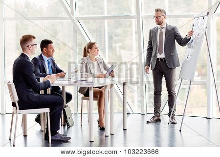 Experienced businessman by whiteboard explaining data to colleagues at seminar