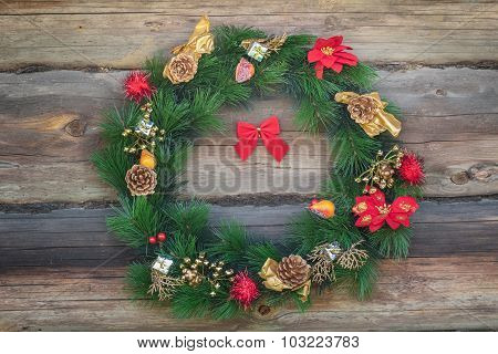 Outdoor Christmas Conifer Wreath At Old Log Cabin Wall Background