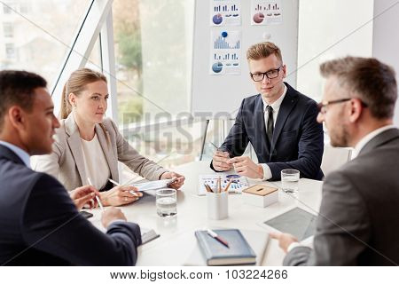 Group of confident colleagues planning work at meeting