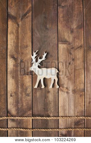 Toy reindeer over two ropes on wooden background