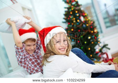 Happy girl in Santa cap looking at camera on background of her brother on Christmas evening