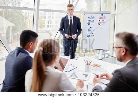 Young businessman standing by board and listening to his colleagues opinion about his presentation