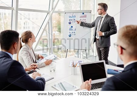 Elegant businessman by whiteboard explaining his viewpoint upon financial fluctuation to his employees