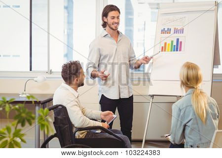 Confident businessman giving presentation to colleagues in creative office