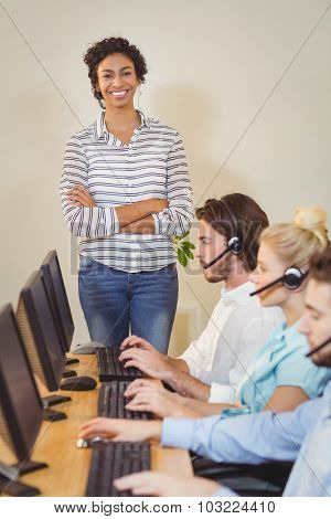 Portrait of smiling businesswoman with arms crossed standing at employees working in call center