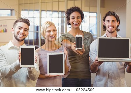 Portrait of happy business colleagues showing technologies in creative office