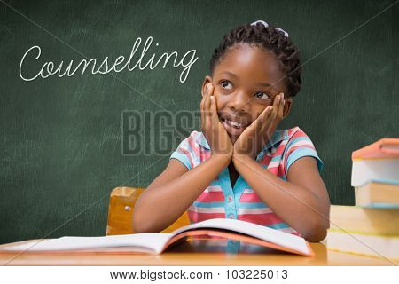 The word counselling and pupil sitting at her desk against green chalkboard
