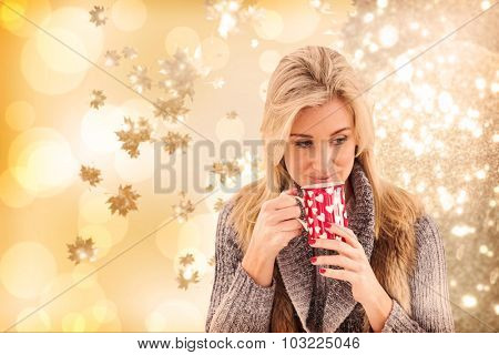 Woman in winter clothes holding a mug against autumnal leaf pattern