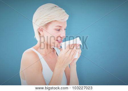 Sick blonde sneezing against blue background