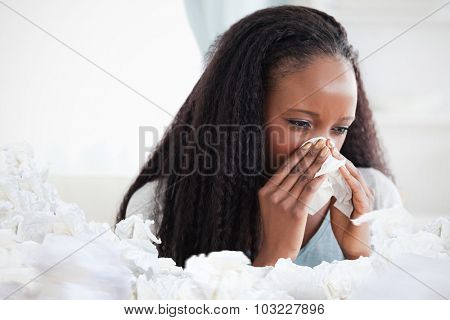 Close up of woman blowing her nose against used tissues