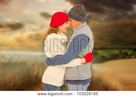 Happy couple in warm clothing hugging against country scene